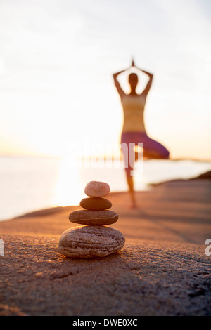 Pile of stones with woman practicing yoga in background at lakeshore - Stock Photo