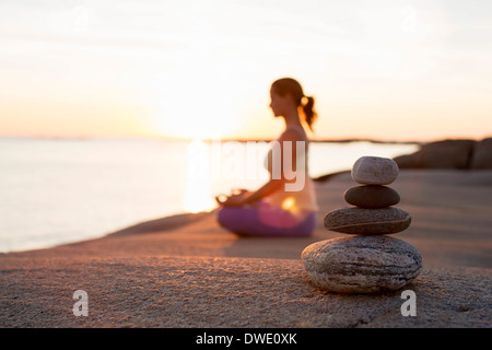 Side view of woman sitting in lotus position on lakeshore with focus on stack of stones - Stock Photo