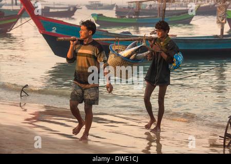Burmese men bringing the nights catch ashore at dawn, near the fishing village of Ngapali Beach - Myanmar (Burma) - Stock Photo