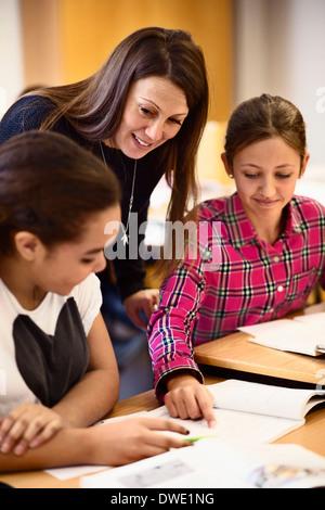 Teacher assisting schoolgirls in classroom - Stock Photo