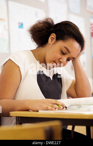 High school girl reading book at desk in classroom - Stock Photo