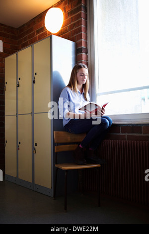 Schoolgirl studying by window in locker room - Stock Photo