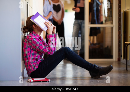 Side view of bored schoolgirl covering face with book in locker room - Stock Photo