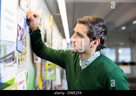 Male student reading notice board in college - Stock Photo
