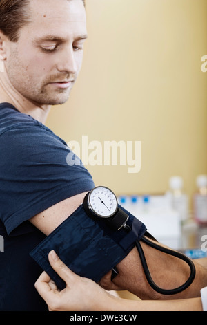 Doctor putting blood pressure cuff on male patient's arm in clinic - Stock Photo