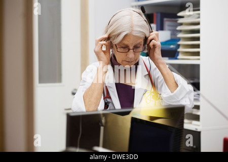 Senior female audiologist wearing headphones in examination room - Stock Photo