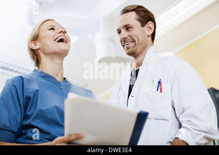 Happy doctor with nurse holding report in hospital - Stock Photo
