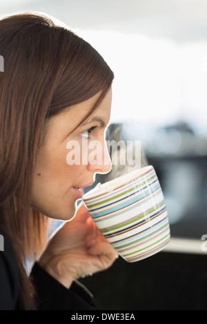Businesswoman having coffee in office - Stock Photo
