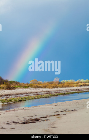 Beautiful colourful rainbow in the colours of the spectrum arcing over over tidal mud flats at the coast with distant - Stock Photo