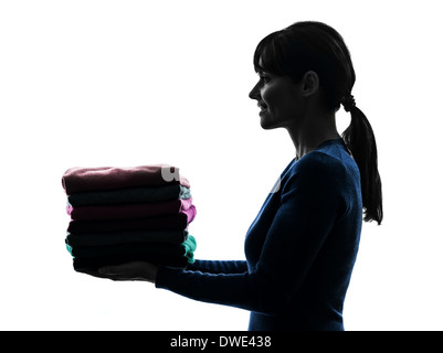 one  woman maid holding sweater pile cleaning in silhouette studio isolated on white background - Stock Photo