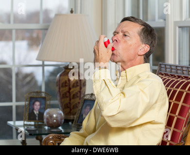 Senior, late middle-aged man at home using an asthma inhaler - Stock Photo