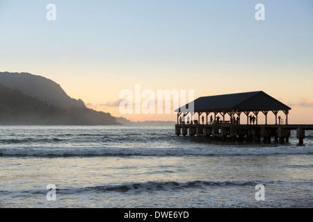Hanalei Bay, Kauai, Hawaii, USA - Sightseers on Hanalei Pier at dawn with the Na Pali mountains - Stock Photo