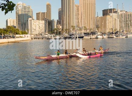 Honolulu, Hawaii, USA - Group of boys and girls paddle an outrigger Hawaiian canoe in the harbor by Ala Moana beach - Stock Photo