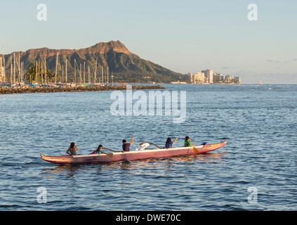 Honolulu, Hawaii, USA - Group of boys and girls paddle an outrigger Hawaiian canoe in the harbor of Honolulu - Stock Photo