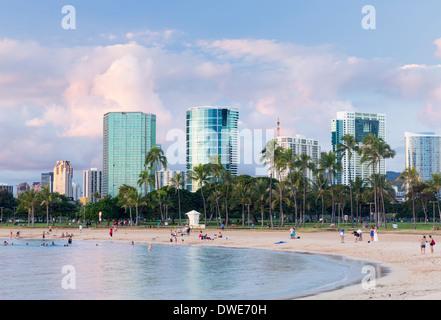 Skyline of Honolulu over the beach from Ala Moana Beach park, Hawaii, at sunset - Stock Photo