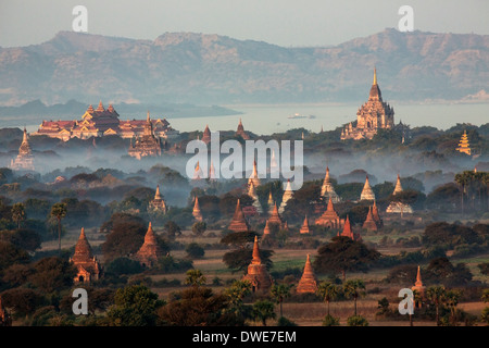 The temples of the Archaeological Zone in Bagan in the early morning sunlight. In the distance is the Irrawaddy - Stock Photo