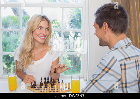Couple playing chess while having orange juice at home - Stock Photo