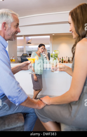 Cropped couple toasting cocktails with woman in background - Stock Photo