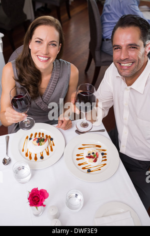 Young couple with wine glasses dining in restaurant - Stock Photo
