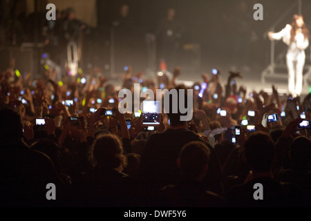 Concert crowd using technology including mobile phones, cell phones, iPhones, iPad's and electronic devices to photograph, - Stock Photo