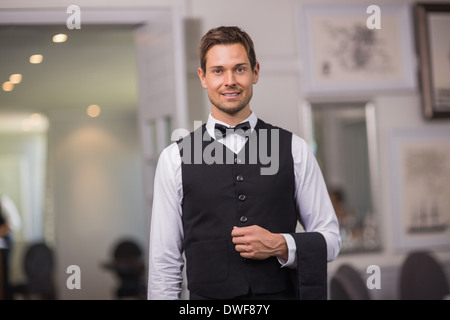 Handsome waiter smiling at camera - Stock Photo
