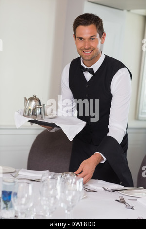 Happy waiter holding tray and setting table - Stock Photo