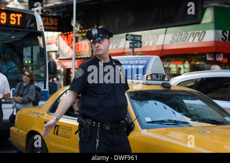A policeman directs traffic near Times Square. 1560 Broadway, between 46th and 47th Street - Stock Photo