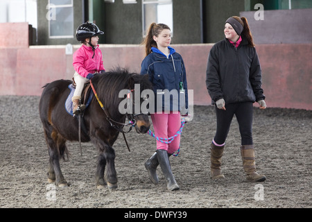 A four year old girl riding a pony during a riding lesson in North Lincolnshire, England, 2014 - Stock Photo