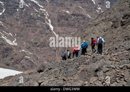 A group descending from summit of Toubkal, Morocco after a successful ascent - Stock Photo