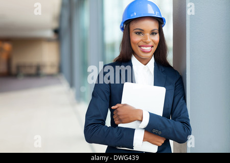 beautiful African construction engineer holding laptop computer - Stock Photo