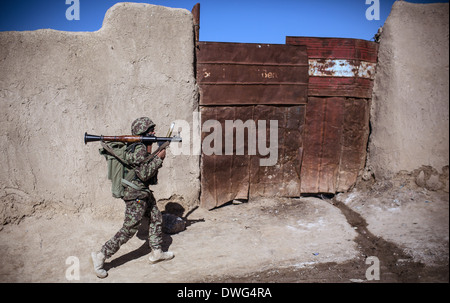 An Afghan National Army soldier armed with a Rocket Propelled Grenade patrols a village during Operation Alamo Scout - Stock Photo