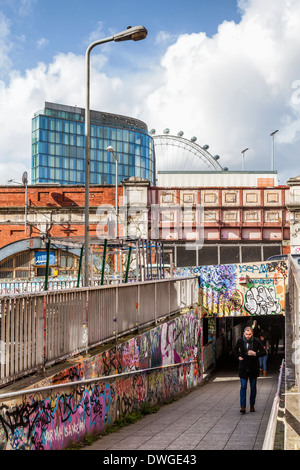 Man walks out of graffiti covered tunnel under Waterloo railway station, buildings and London Eye - Southwark, South - Stock Photo