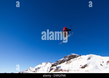 Amateur skier performing jump in snowpark with blue sky in the background. Trademarks have been removed. - Stock Photo