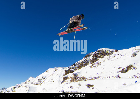 Skier performing jump at ski resort. Trademarks have been removed. - Stock Photo