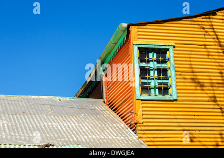 Old orange building set against a blue sky in La Boca neighborhood of Buenos Aires - Stock Photo