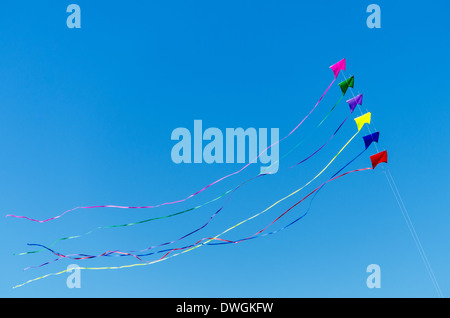 Rainbow colored kites flying against a beautiful blue sky - Stock Photo