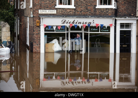 Shopkeeper phones the insurance company after the River Ouse floods the streets of central York in the United Kingdom - Stock Photo