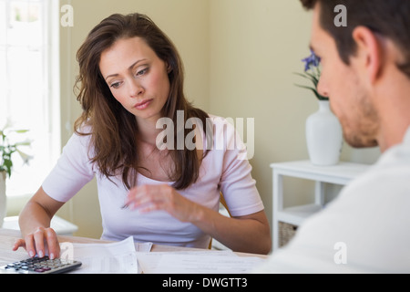 Woman and man sitting with home bills at table - Stock Photo