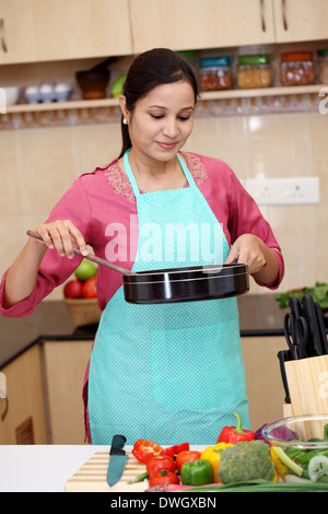 Young Indian woman preparing a dish in her kitchen - Stock Photo