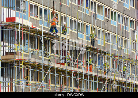 Scaffolders working on one of the empty Heygate Estate high rise social housing blocks in preparation for demolition - Stock Photo
