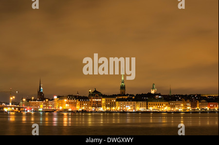 Evening view of the quay, Skeppsbrokajen, Gamla Stan, the old town of Stockholm, Sweden.  Seen from Södermalm. - Stock Photo