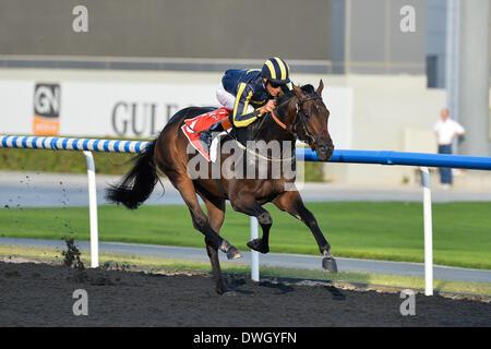 DUBAI, UAE, 8th Mar 2014. ASMAR ridden by Richard Hughes wins the Al Bastakiya race at Meydan as part of Super Saturday - Stock Photo