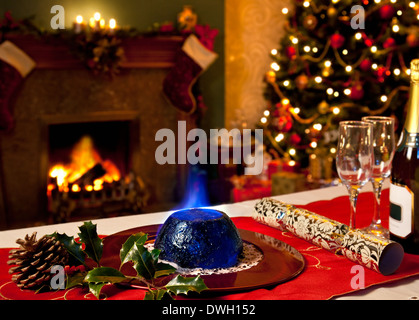 A Christmas Pudding with burning brandy topping with a festive background of fireplace and Christmas tree. - Stock Photo