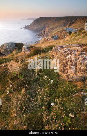 A hazy sun sets over Sennen Cove at Land's End, Cornwall in Summer. - Stock Photo