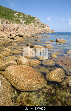 Round boulders cover the cove bed on a sunny summer day at Penberth Cove, Cornwall, England. - Stock Photo