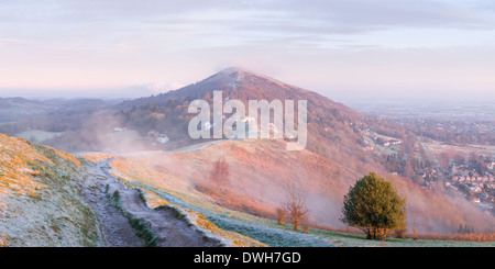 A heavily worn footpath on Perseverance Hill, Malvern Hills, is cast in shadow from the strong light of sunrise. - Stock Photo