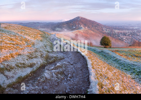 A heavily worn footpath on Perseverance Hill, Malvern Hills, is cast in shadow from the first light of sunrise. - Stock Photo
