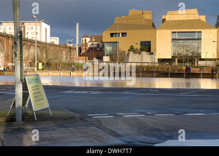 A sign advising motorists that the car park is liable to flooding is placed in a flooded car park. - Stock Photo