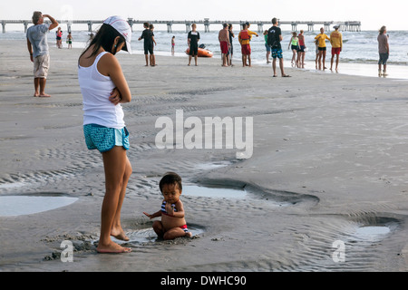 Mother watching young, female Eurasian toddler child wearing two-piece bathing suit, playing in the sand on Jacksonville - Stock Photo