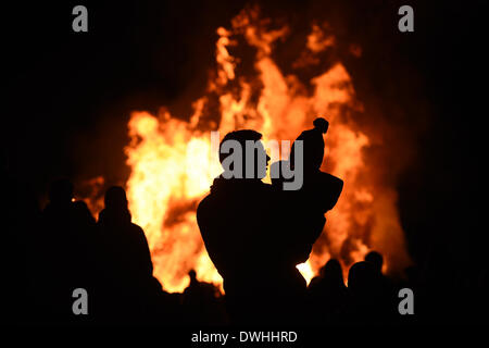 Langenargen, Germany. 08th Mar, 2014. A man holding a child stands in front of a bonfire on the shores of Lake Constance - Stock Photo